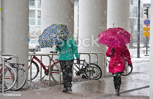 Espoo, Finland – April 16, 2020: Pedestrians equipped with umbrellas. Spring day has turned to snowfall. Finland.