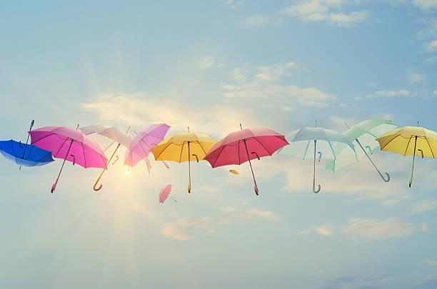 umbrellas line-up across the sky - umbrellas stock photos and pictures