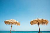Two straw umbrellas at Pachena beach (Milos Island, Cyclades, Greece).