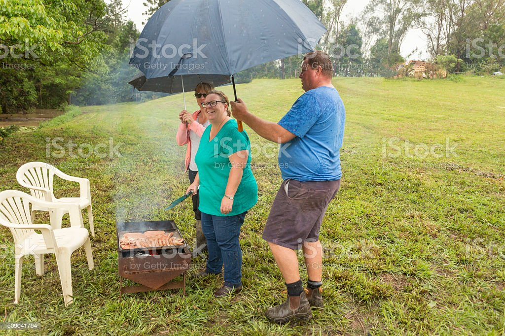 Umbrellas being held over an Australian woman cooking a barbeque meal...