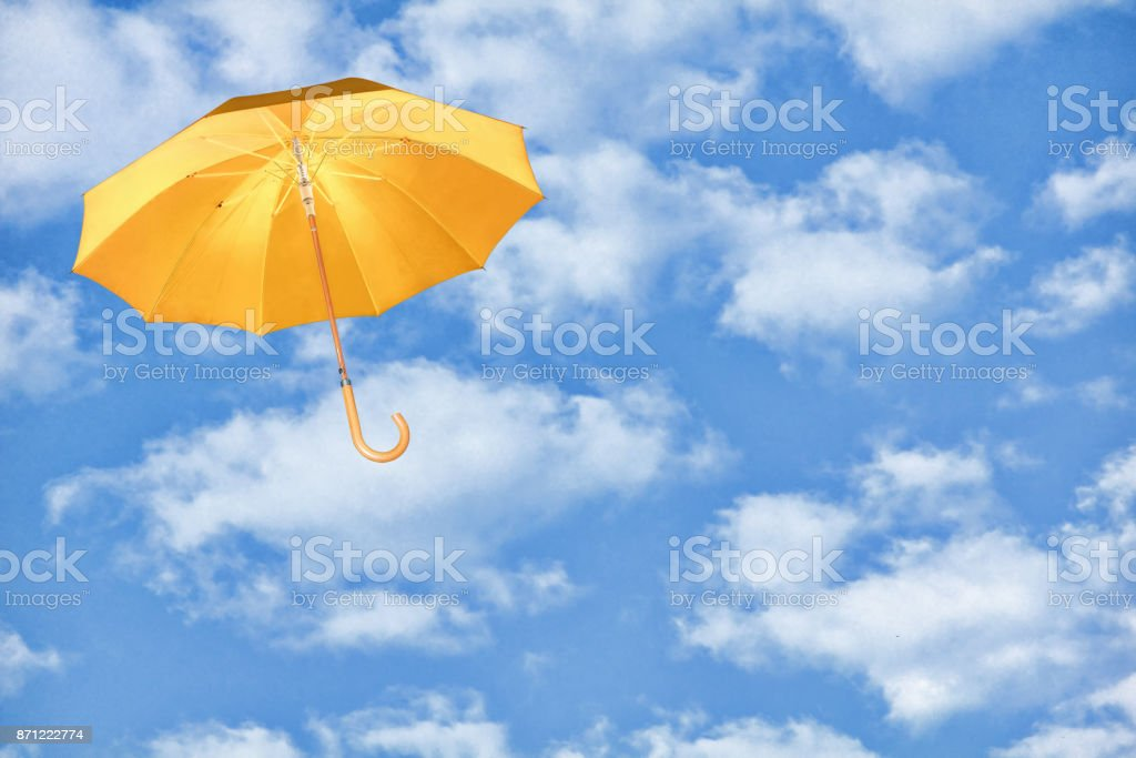 Umbrella.Yellow umbrella flies in sky against of white clouds. stock photo