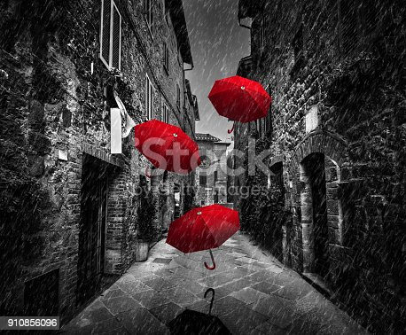 istock Umrbellas flying with wind and rain on dark street in an old Italian town in Tuscany, Italy 910856096