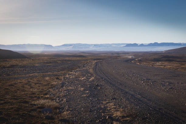 un auto corre su un polveroso percorso sterrato in islanda nell'arido panorama islandese, un'auto sopraggiunge alzando una nuvola di polvere da una strada sterrata percorso stock pictures, royalty-free photos & images