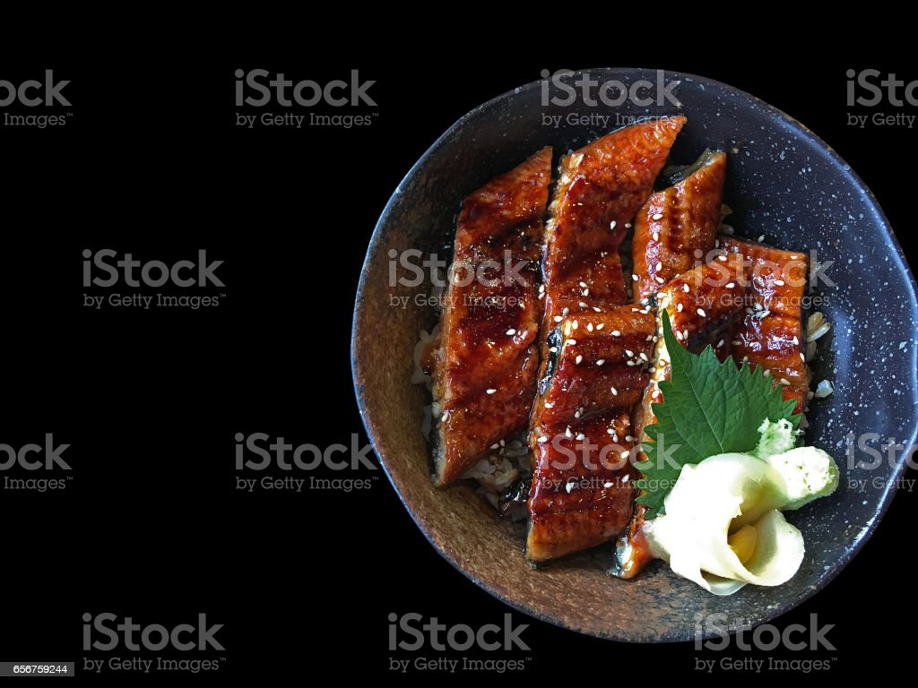 Unagi don (Unadon), steamed white rice topped with fillet of freshwater eel grilled, Japanese food on black background, top view. stock photo