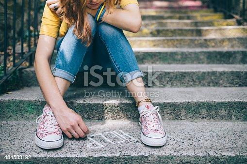 Teenage grl sitting on a staircase outside feeling depressed