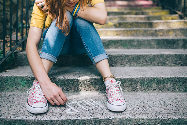 Unahppy girl writes help on the ground Teenage grl sitting on a staircase outside feeling depressed post traumatic stress disorder stock pictures, royalty-free photos & images