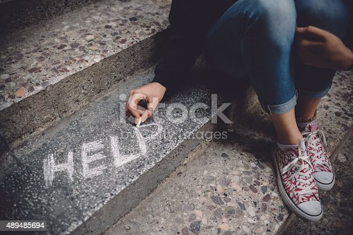 Teenage girl sitting on a staircase outside feeling depressed