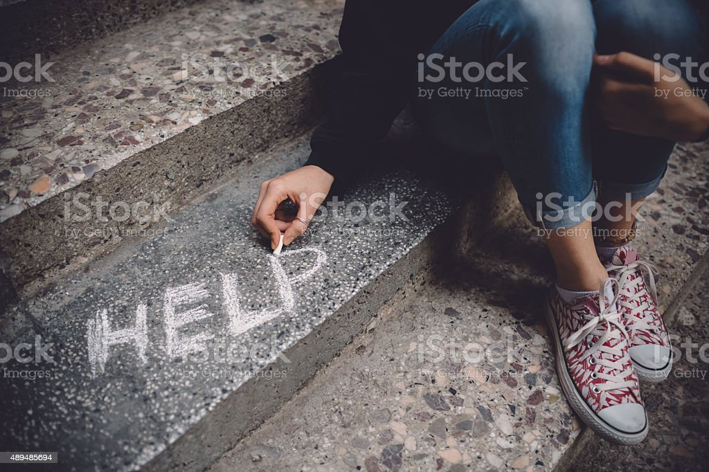 Unahppy girl writes help on the ground stock photo