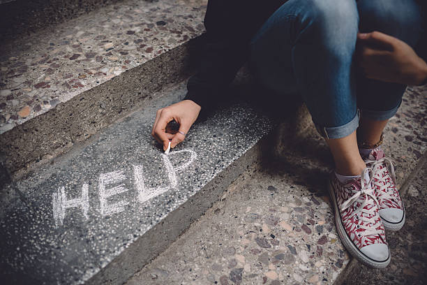 Unahppy girl writes help on the ground Teenage girl sitting on a staircase outside feeling depressed hopelessness stock pictures, royalty-free photos & images