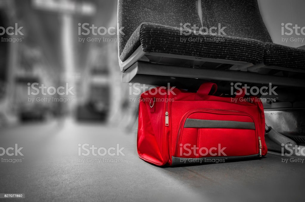 Unattended red bag left in a subway cart, train carriage or monorail. stock photo