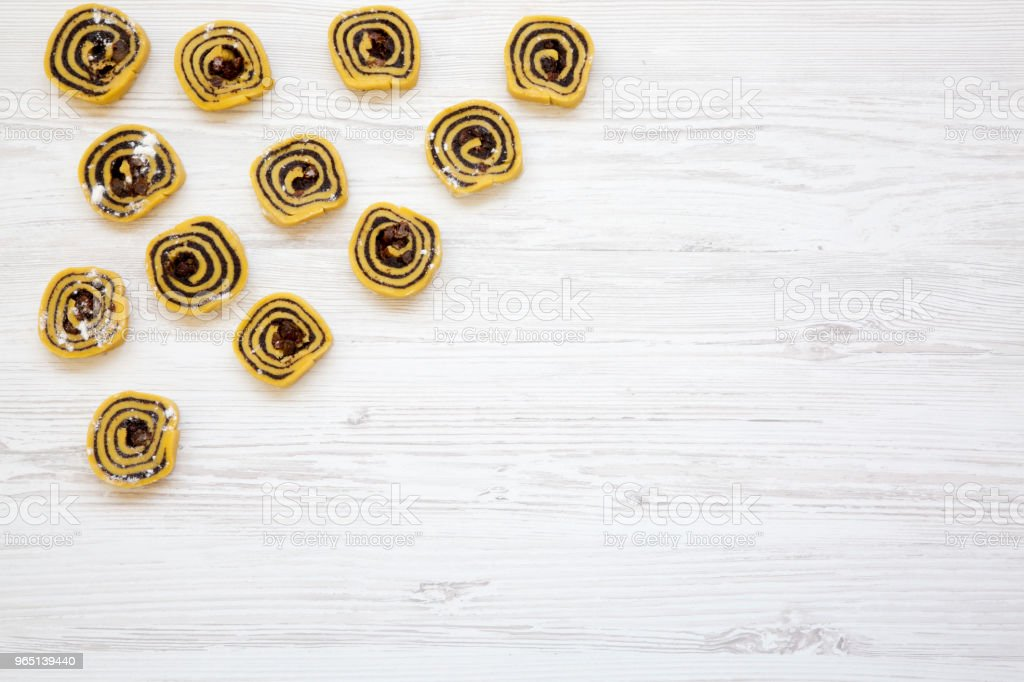 Unbaked cookies with poppy seeds, raisins on white wooden table, top view. From above, flat lay. Space for text. royalty-free stock photo