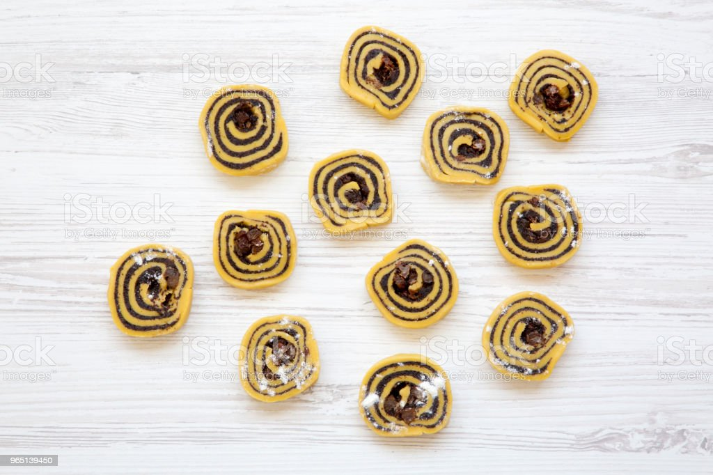 Unbaked cookies with poppy seeds, raisins. White wooden table, top view. From above, flat lay. Copy space. zbiór zdjęć royalty-free
