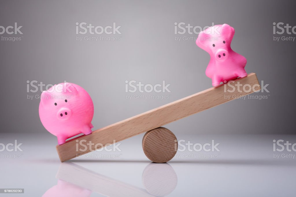 Unbalance Of Two Piggybanks On Wooden Seesaw stock photo