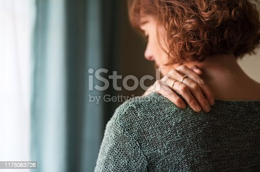 Rear view shot of a woman suffering from a shoulder pain