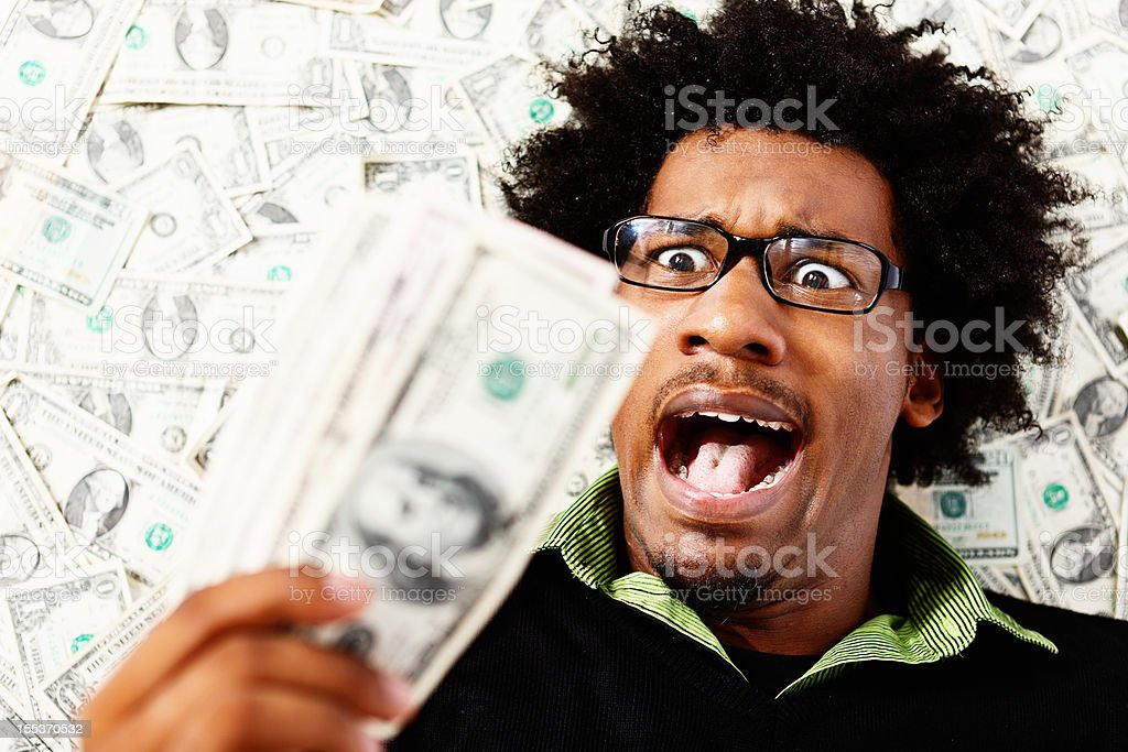 Unbelievable! Astonished young geek with thousands of dollars stock photo