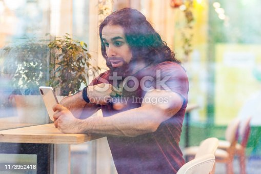 Portrait through the window of unbelievable handsome young adult muscular man with curly long hair sitting on cafe, holding phone with shocked face pointing finger to self, talking through web camera.