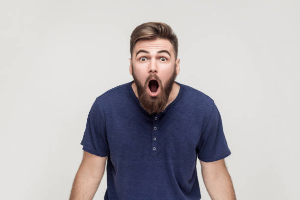 Unbelievable news! Young adult man open mouth and shocked Unbelievable news! Young adult crazy man with opened mouth looking at camera. Studio shot, gray background anchor athlete stock pictures, royalty-free photos & images