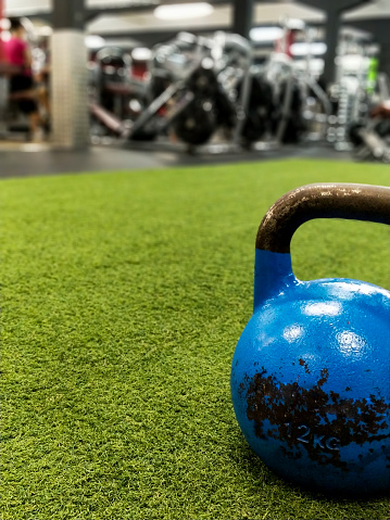 istock Unbranded blue kettle-bell on artificial grass in a gym 1133651680