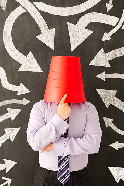 Uncertain businessman Businessman with wastepaper bin over their head shot against a chalkboard with hand drawn chalk arrows head in the sand stock pictures, royalty-free photos & images