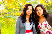 Two Latina twin sisters gaze into the camera apprehensively.RELATED IMAGES:
