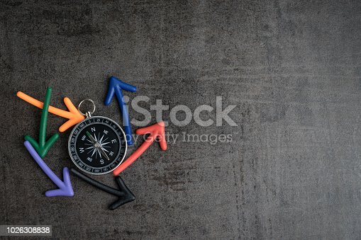 Uncertain path or multiple random life fortune and directions concept, compass at the center with magnet arrows pointing random multi directions on dark black chalkboard cement wall with copy space.