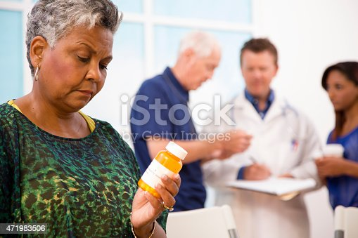 istock Uncertain senior woman abuses prescription medications. Doctor, patients background. 471983506