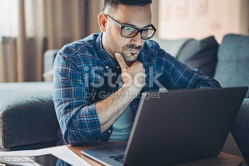 Worried man in front of a laptop at home