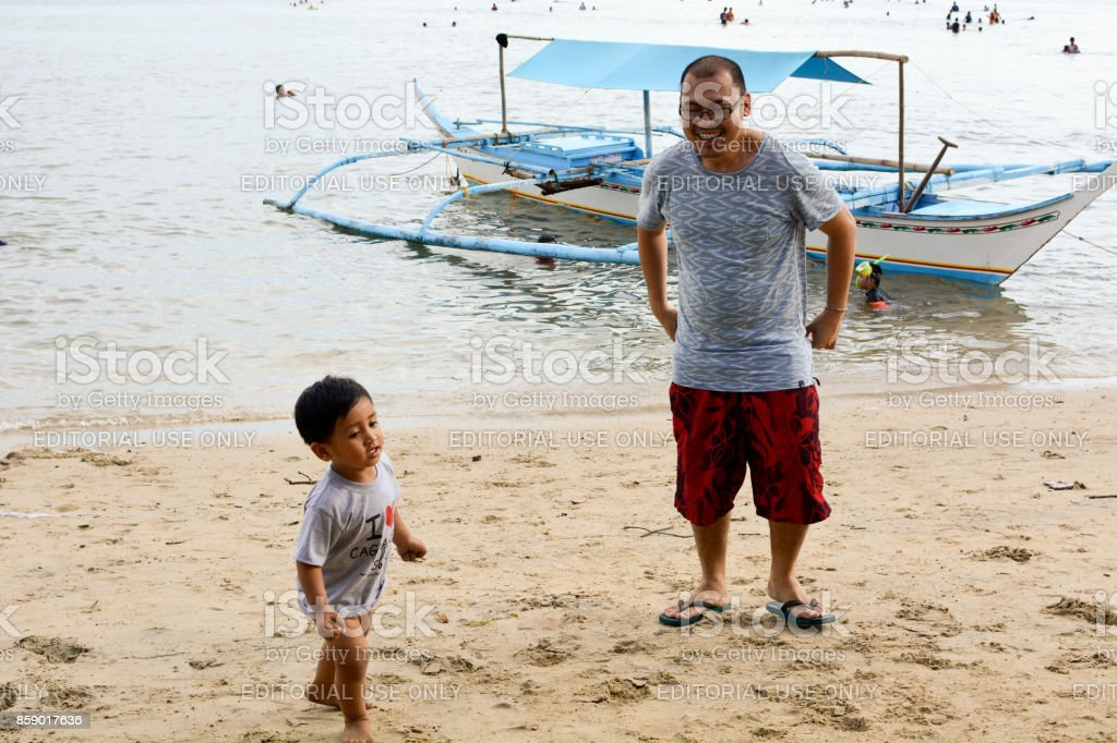 Uncle and baby nephew having fun chasing on white sand beach boat behind stock photo