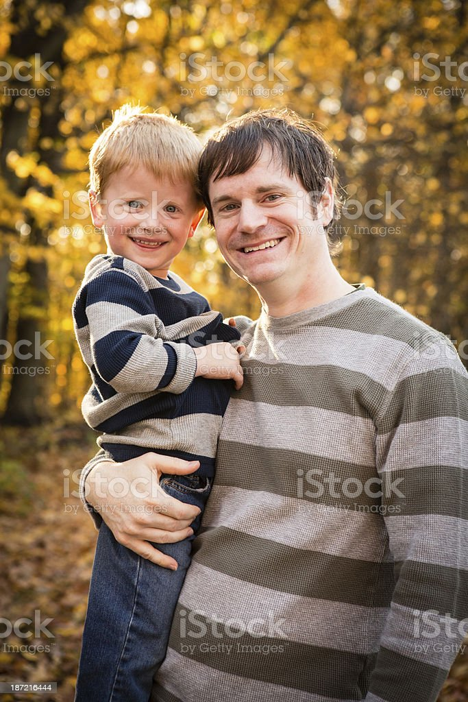Uncle Holding His Little Nephew Outdoors in Autumn Woods royalty-free stock photo