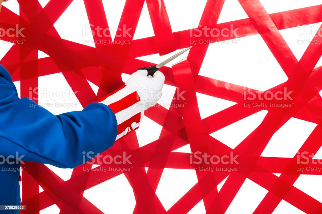 Uncle Sam cutting through a wall of red tape against a white background stock photo