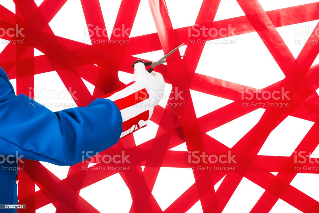 Uncle Sam getting ready to cut through a wall of red tape against a white background stock photo