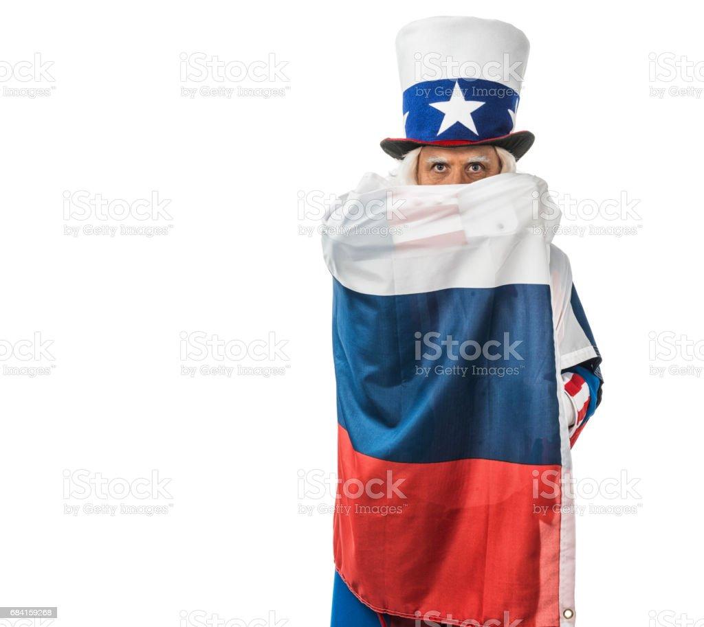 Uncle Sam gömmer sig bakom en rysk flagga han håller upp framför ansiktet royaltyfri bildbanksbilder