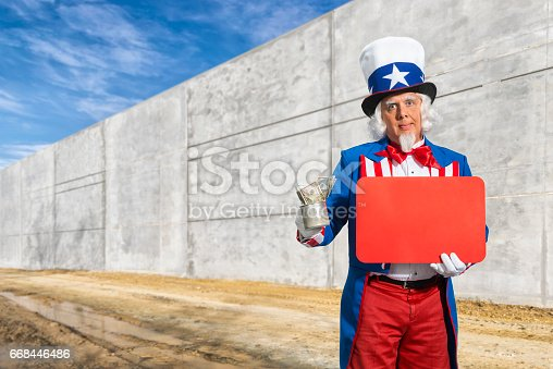 istock Uncle Sam looking for donations to pay for the wall on the Mexico border 668446486