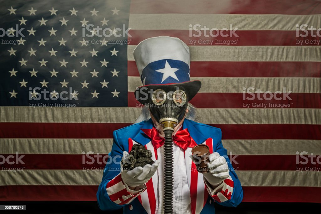 Uncle Sam wearing gas mask holding coal and a oil drum stock photo