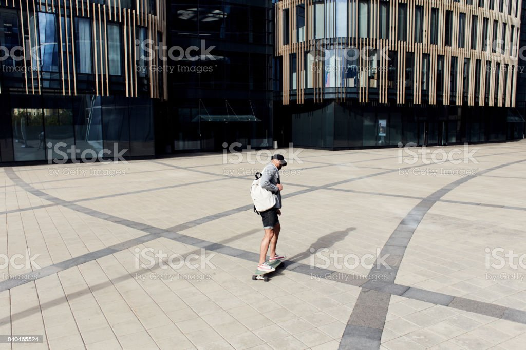 Uncommon businessman on skateboard stock photo