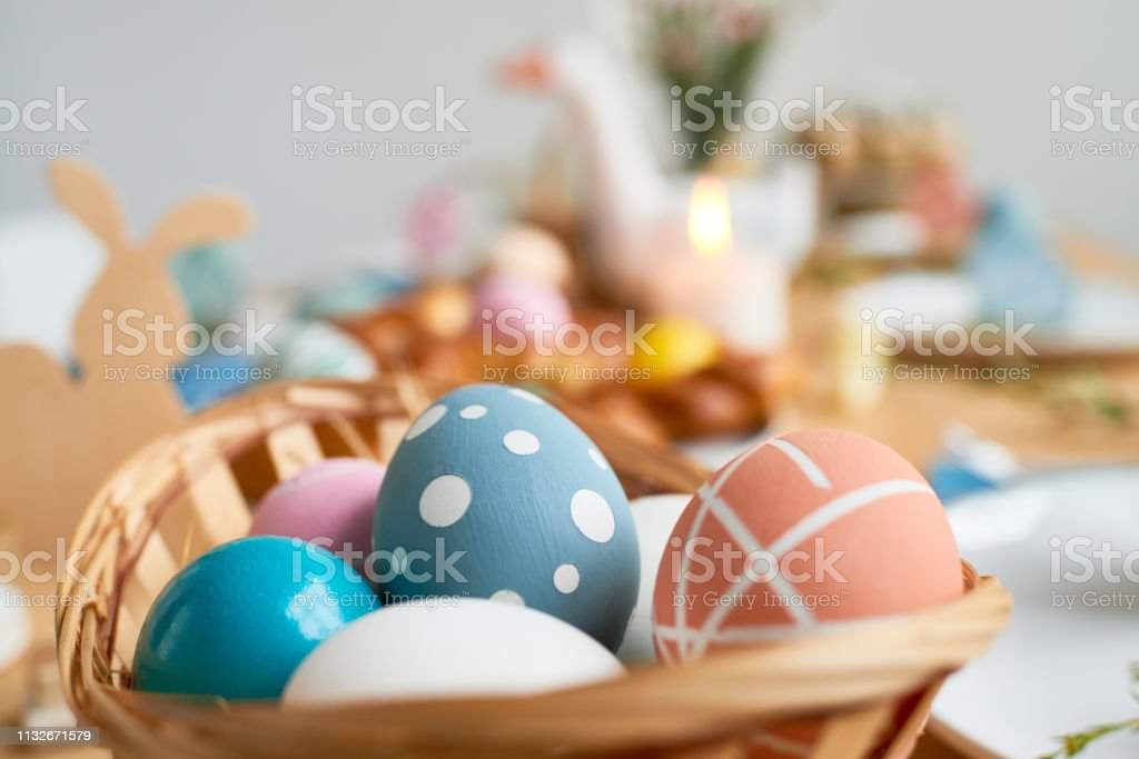 Uncommon design for Easter eggs: close-up of painted eggs with dots and stripes in wicker basket on dining table