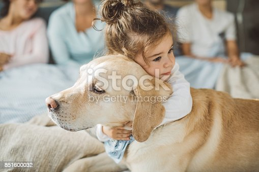 Little boy hugging his dog friend on bed in the morning