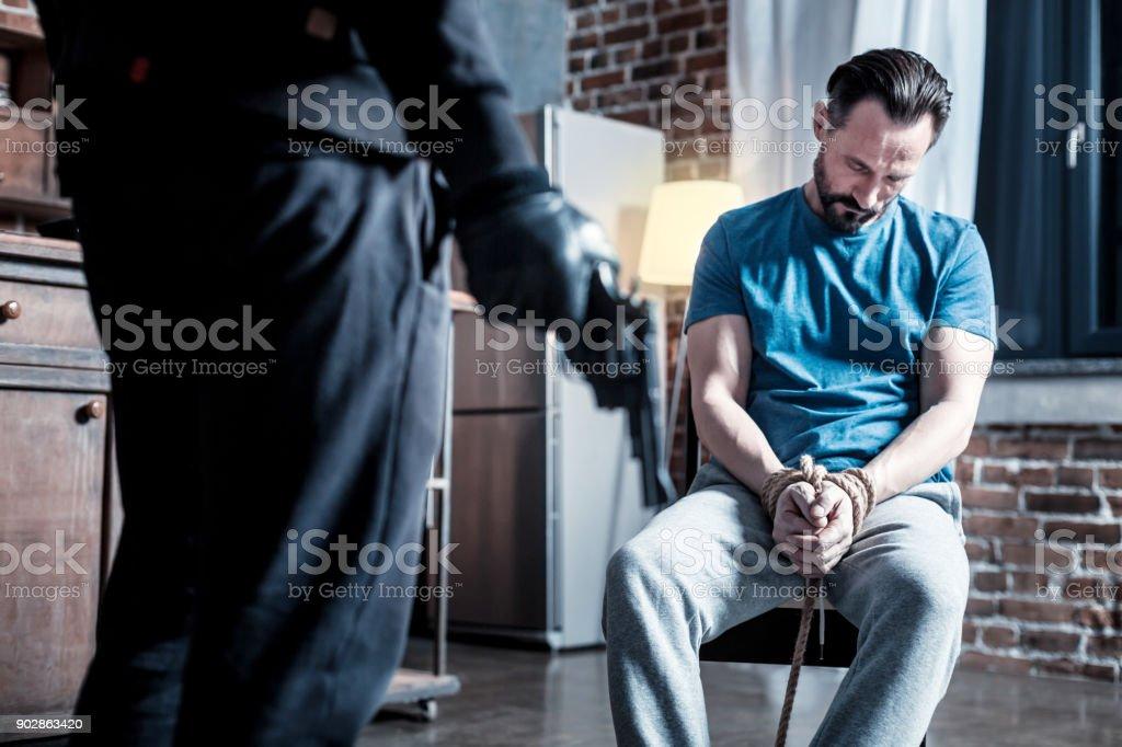 Homem inconsciente e um criminoso em pé perto dele - foto de acervo