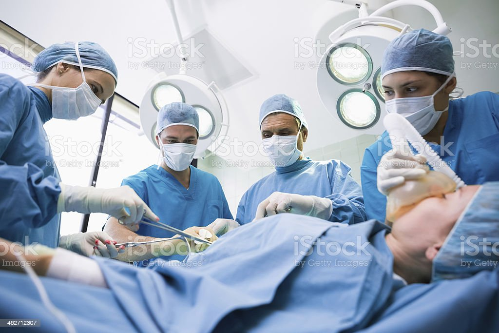 Unconscious patient being operated stock photo