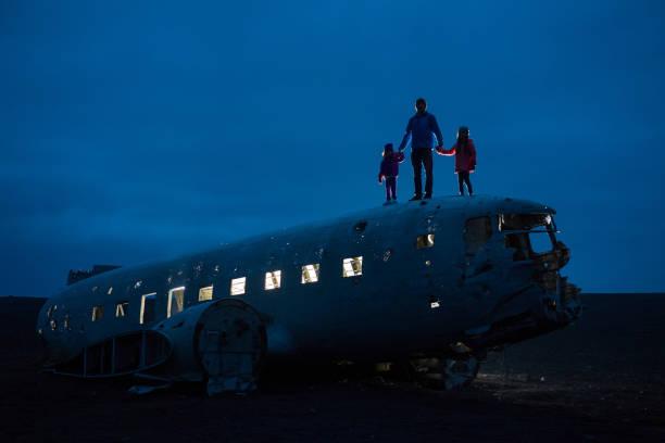 Unconventional Family Portrait Family visiting Sólheimasandur Plane Crash in Iceland sólheimasandur stock pictures, royalty-free photos & images