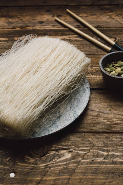Uncooked Asian rice noodles, wooden background Uncooked Asian rice noodles, in the marble dish, on the wooden rustic table rice noodles stock pictures, royalty-free photos & images