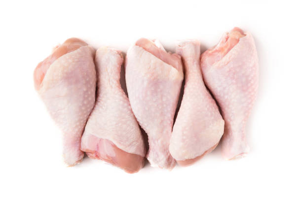 Uncooked chicken legs on white background Uncooked chicken legs in row isolated on white background, top view drumstick stock pictures, royalty-free photos & images