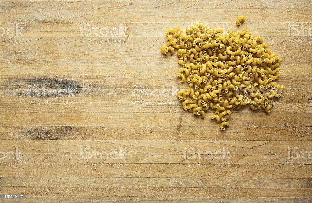 Uncooked Elbow Macaroni on Cutting Board stock photo
