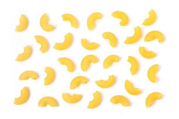 uncooked elbow macaroni on white background - macarrão imagens e fotografias de stock
