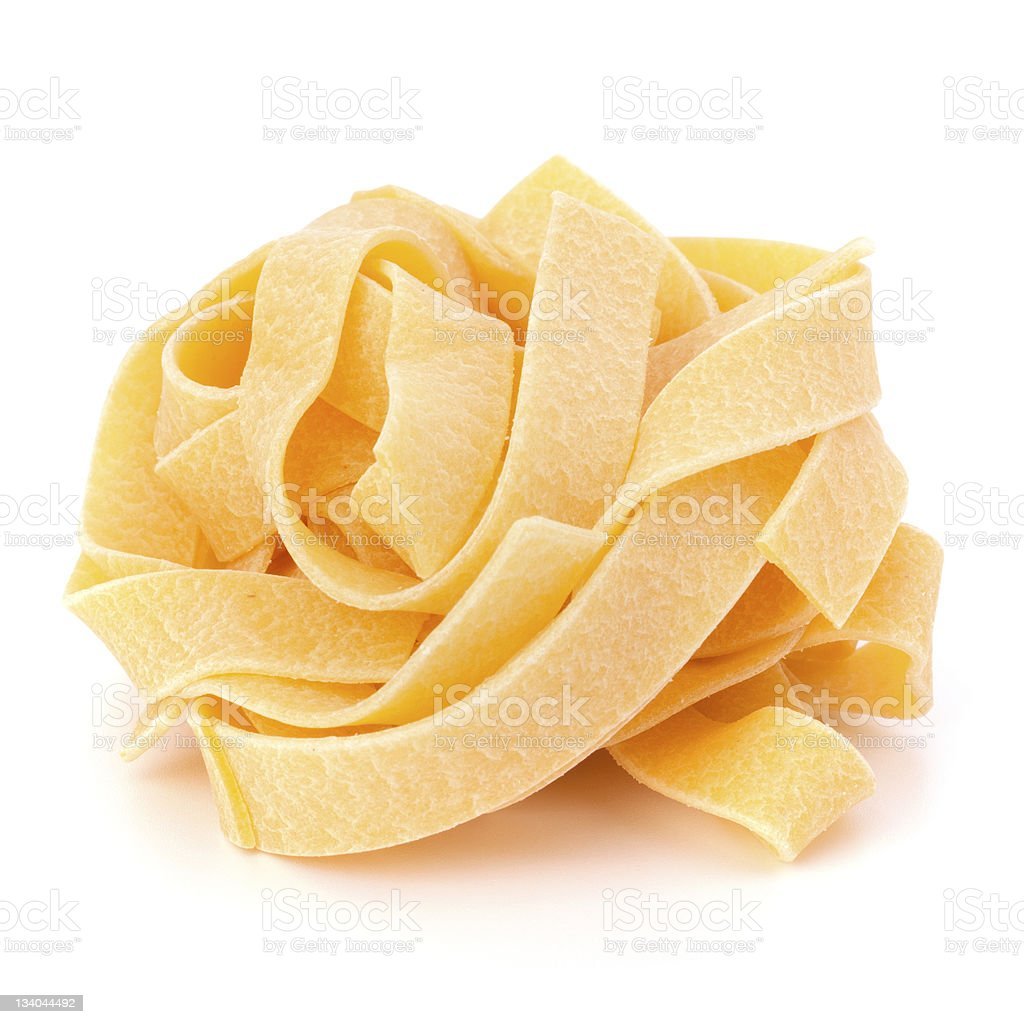 Uncooked fettuccine pasta white background stock photo