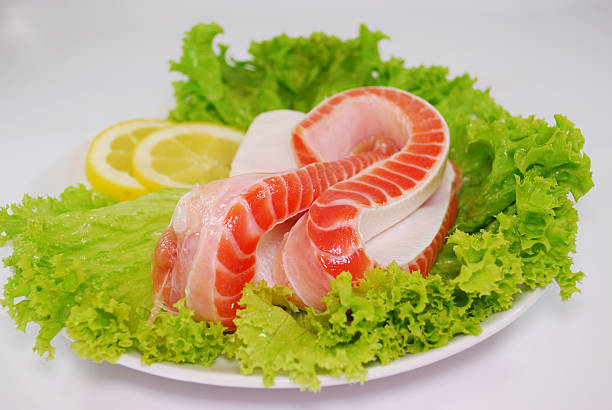 Uncooked Fresh Salmon Bellies decorated with salad and lemon slices – Foto
