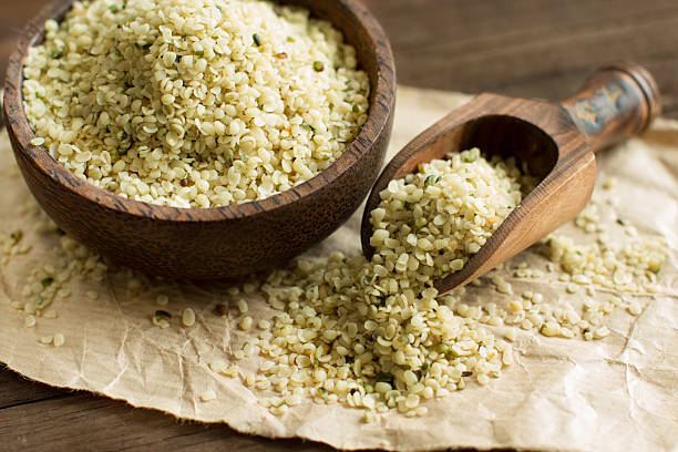 Uncooked Hemp seeds in a bowl with a spoon stock photo