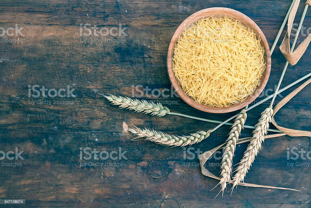 Uncooked Italian pasta Capellini in wooden pot royalty-free stock photo