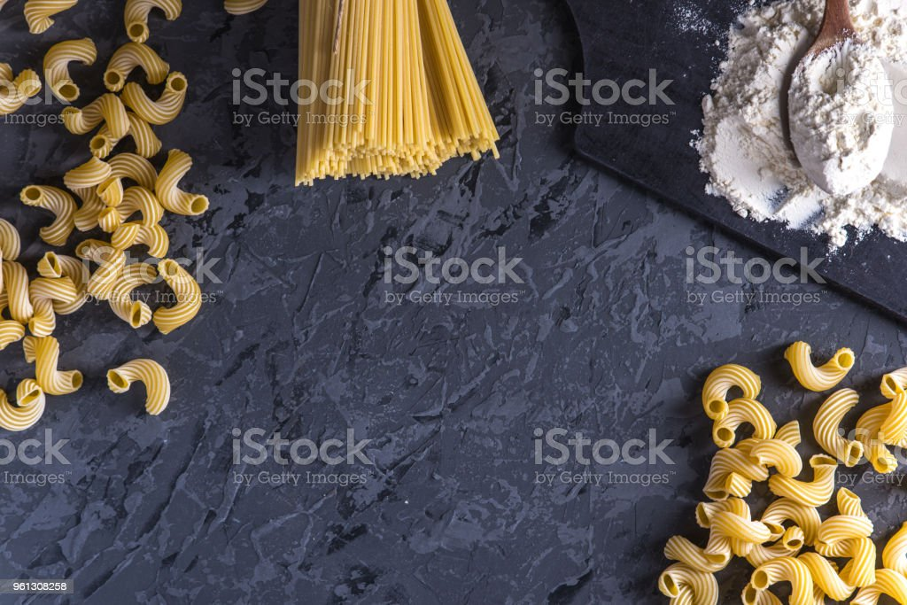 Uncooked italian pasta spaghetti and cavatappi with flour from durum wheat. Concept of The composition of food design. stock photo
