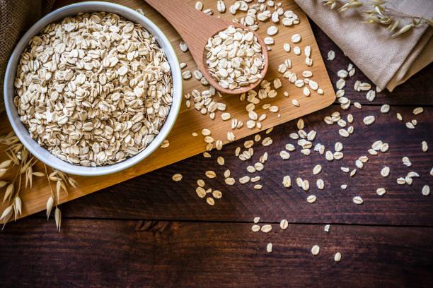 uncooked oat flakes in bowl - fotos de oats imagens e fotografias de stock